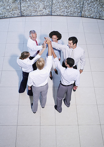 Leadership team joining hands in a display of team-building unity